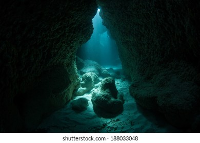 Sunlight penetrates the sea and illuminates a dark crevice at a dive site known as Yap Caverns. Dark niches such as this provide habitat to many shade-loving marine species.
