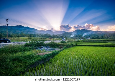 Sunlight rays burst through clouds in the morning in a beautiful farm village on a sunny day