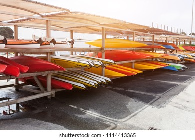 In sunlight, red, yellow and white kayaks placed upside down on metal storage racks. Stocked canoe in the Brest, France 28 May 2018.