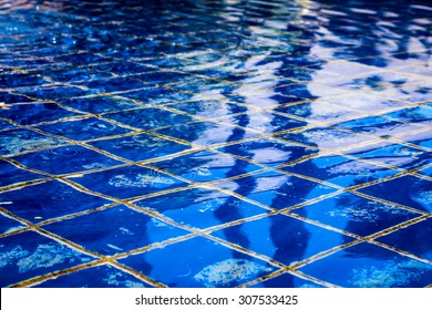 Sunlight reflecting off of a clear tile pool on a summer day.