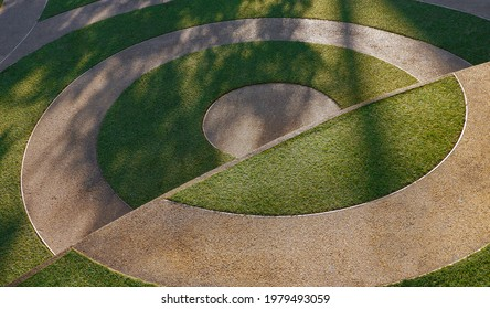Sunlight and shadow of branches on circle pattern of artificial green turf and gravel stone in different level pavement floor in public park area