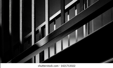 Sunlight and shadow on railing and banister surface of metal staircase in black and white with dark tone style, architecture concept