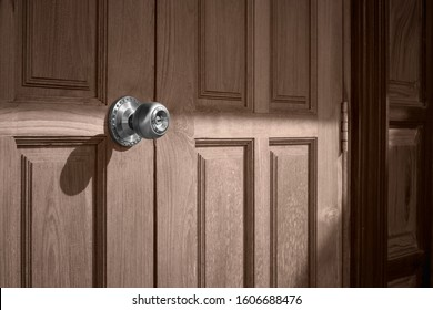 Sunlight and shadow on surface of doorknob on teak wood door in vintage tone style, home exterior architecture concept