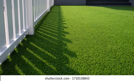 Sunlight and shadow of white wooden fence on green artificial turf surface in front yard of home, selective focus with high angle view