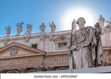 Sunlight in the shape of a round halo behind the head of the statue of St. Paul the Apostle against the background of St. Peter's Basilica in the Vatican, Rome, Italy.