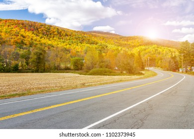 Sunlight shines above empty highway road through colorful fall forest landscape in New England