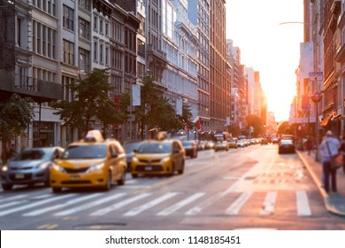 Sunlight shines down the streets of New York City with taxis stopped at the intersection