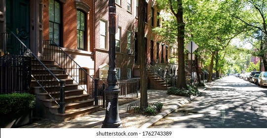 Sunlight shines on a block of historic brownstone buildings in the East Village neighborhood of Manhattan in New York City NYC