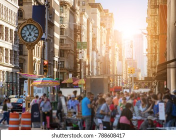 Sunlight shines on the buildings of Manhattan with crowds of people shopping at street vendors in New York City