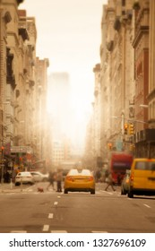 Sunlight shines on New York City urban street with anonymous blurred people, cars and yellow taxi cabs