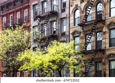 Sunlight shines on trees in front of historic old buildings on 3rd Avenue in the East Village of Manhattan, New York City NYC