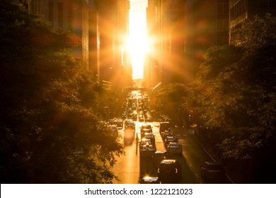 Sunlight shines overhead on the buildings and traffic on 42nd Street through Midtown Manhattan, New York City