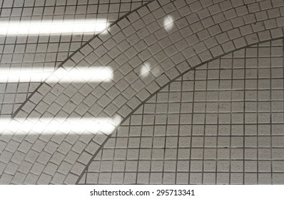 Sunlight shines through building creating rectangles on geometric tiled ground