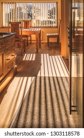 sunlight shining into a kitchen through vertical blinds casting a long striped shadow on the wooden floor and across the oak kitchen table and chairs
