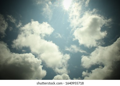 Sunlight shining through fluffy white clouds against a blue sky