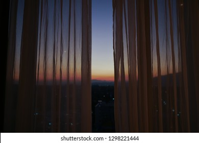 sunlight through curtain with twilight sunset sky view outside the window