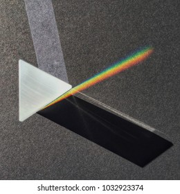 Sunlight through prism on dark background scattering rainbow spectrum, shadow and light shapes