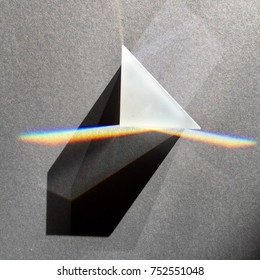 Sunlight through prism scattering in rainbow, light shapes and shadows