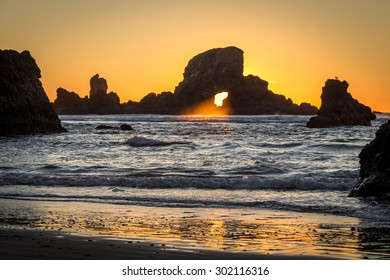 Sunlight through a rock at the Oregon Coast. Sunset beach goonies ocean shore