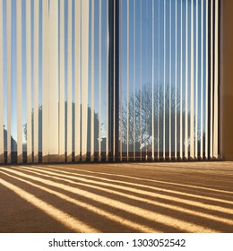 sunlight through vertical blinds angled slightly open hanging over large sliding interior glass doors and throwing a striped shadow on to a beige carpet