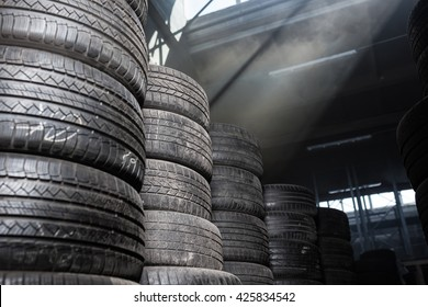 Sunlight in the tire storage. Stack of old tires in a car shop garage. Tire installation service.