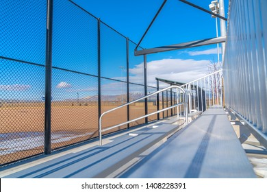 Sunlit bleachers overlooking a vast sports field on the other side of the fence