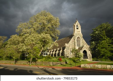 Sunlit Church against stormy sky. Church of the New Jerusalem (Swedenborg Chapel), Cambridge, Massachusetts, United States.