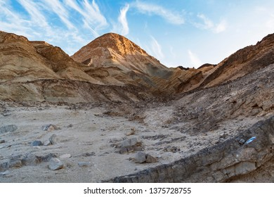 a sunlit desert mountain peak in the eilat mountains near the gulf of eilat akaba with wispy clouds in a blue sky