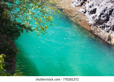 Sunlit emerald whitewater of mountain river