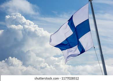 sunlit Finnish flag flying in the wind against the sky with large clouds