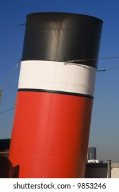 Sunlit funnel from a steamship in red, white and black