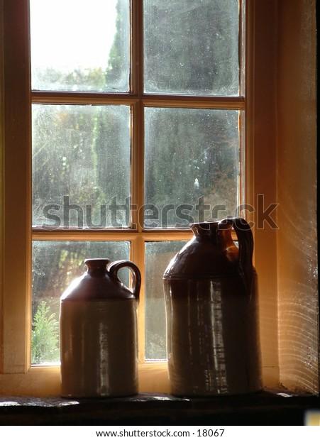 Sunlit jugs in pub window
