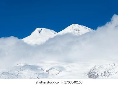 Sunlit Mount Elbrus in clouds. Caucasus mountains winter scenic view.