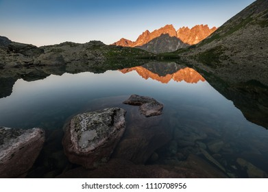 Sunlit mountain peaks are beautifully reflected in the water of a small lake, calm water and blue sky