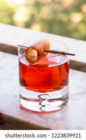Sunlit Negroni Cocktail on Ice with Orange Twist in Glass on Marble Windowsill