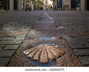 Sun-lit pilgrim's scallop as a trail marker of the Way of Saint James in the old town of Burgos, Castile, Spain
