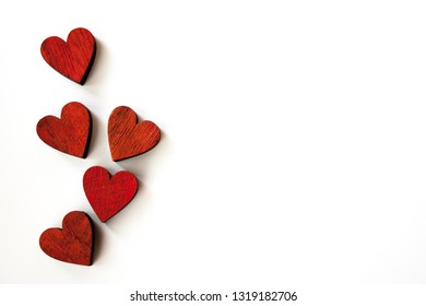 Sunlit red hearts on a white background. Space for text.