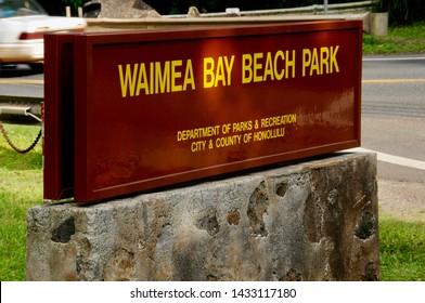 Sunlit sign at the entrance to Waimea Bay Beach Park, Oahu.