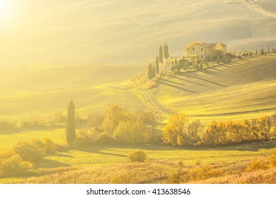 sunlit typical tuscany landscape with grassy field and a house on a warm autumn morning