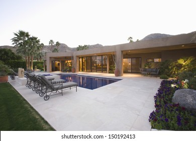 Sunloungers along the pool against modern house and clear sky