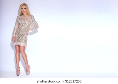 Sunning sexy beautiful young woman blond long hair and of short elegant dress with glowing crystals and iridescent sequins on a white background