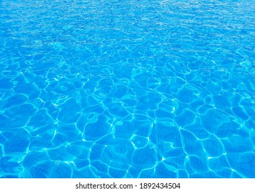 Sunny abstract blue water background. Mobile photography of rippling waterpool