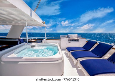 Sunny aft deck of a large, luxurious private motor yacht featuring a hot tub spa, deck chairs, and a barbecue. Blue skies and tropical water add to the concept of living the good life.