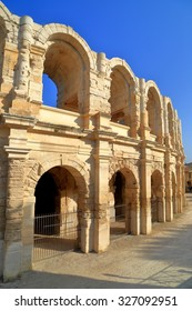 Sunny arches of the ancient Roman amphitheater in Arles, France