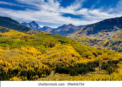 Sunny autumn afternoon view of Capitol Peak near Aspen Colorado surrounded by valley filled with changing yellow Aspen trees and blue sky with wispy clouds
