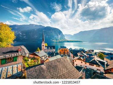 Sunny autumn cityscape of Hallstatt town. Splendid morning viev of Hallstatt lake, Salzkammergut region, Austria, Europe. Traveling concept background.