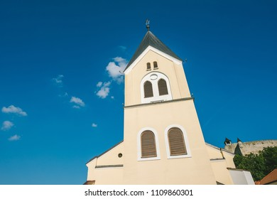 Sunny autumn day in old town of Trencin, Slovakia. Beautiful white church.