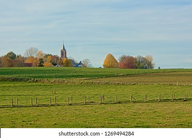 Sunny autumn landscape with meadows and a church tower in between colorful trees in flemish ardennes, Belgium