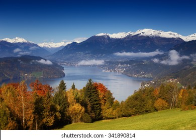 Sunny autumn morning view on Lake Millstatt in Austria, Carinthia. With golden, orange and red trees, small towns and villages on shores and snow-capped mountains in the background.