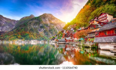 Sunny autumnal day at famous Hallstatt lakeside town reflecting in Hallstattersee lake. Location: resort village Hallstatt, Salzkammergut region, Austria, Alps. Europe.